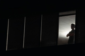 Man looking out office window at night