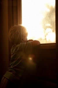 Young boy looking through window