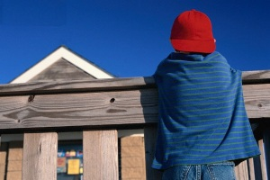 Boy Standing Along a Fence